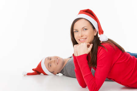 Couple in Santa hats. Cheerful young couple in Santa hat lying on the floor and smiling while isolated on white photo
