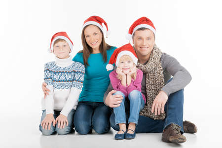 Cheerful family in Santa hats looking at camera and smiling while isolated on white photo