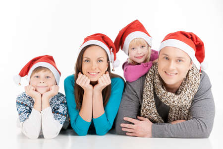 Family on Christmas. Cheerful family in Santa hats looking at camera and smiling while isolated on white photo