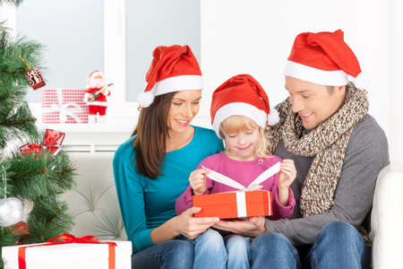 Christmas Eve. Cheerful family opening Christmas gift box and smiling photo