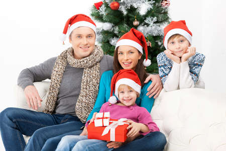 christmas spending: Spending Christmas Eve together. Cheerful family sitting close to each other and smiling Stock Photo