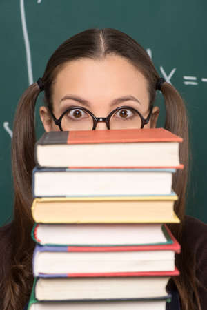 mathematical proof: Book stack. Shocked young women looking out from the book stack while standing in front of the blackboard