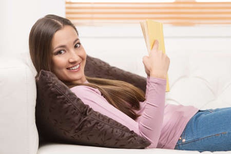 hair back: Relaxing with interesting book. Cheerful young women reading a book while lying down on the couch Stock Photo