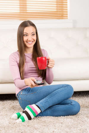 long socks: Relaxing at home. Cheerful young women drinking coffee and watching TV while sitting on the floor Stock Photo