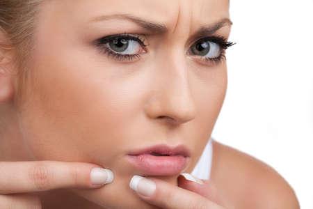mujer decepcionada: Mujer preocupante. Mujer joven decepcionante tocar su cara mientras aislados en blanco