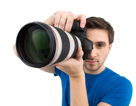 Man with camera. Confident young man holding camera in his hands and focusing while isolated on white photo