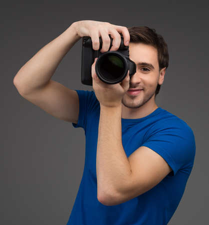 Man with camera. Cheerful young man holding camera in his hands and focusing at you while isolated on grey photo
