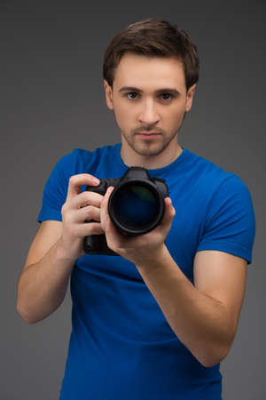 Man with camera. Confident young man holding camera in his hands and looking at you while isolated on grey photo