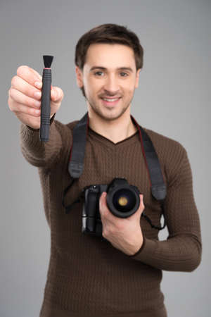 Man with camera and brush. Cheerful young man holding camera and brush for lens in his hands and smiling while standing isolated on grey photo