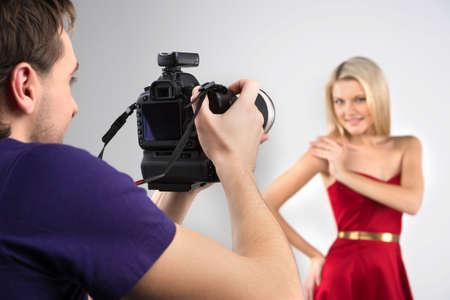 hombre disparando: Fot�grafo y modelo. Joven fotografiando modelo en el estudio
