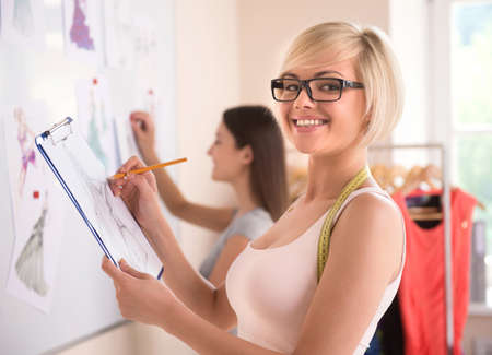 Two beautiful young woman in glasses working in fashion design studio Stock Photo - 22132697