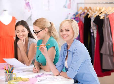 design studio: Fashion designers at work. Three cheerful young women working at fashion design studio