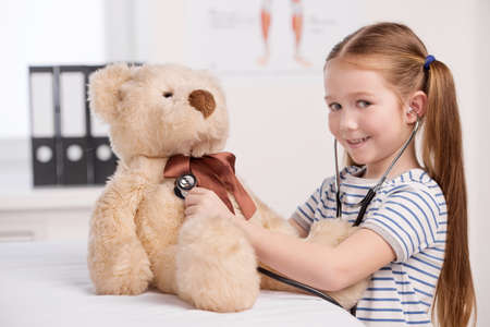 toy bear: Medical exam of toy bear. Cheerful little girl examining her toy bear with stethoscope