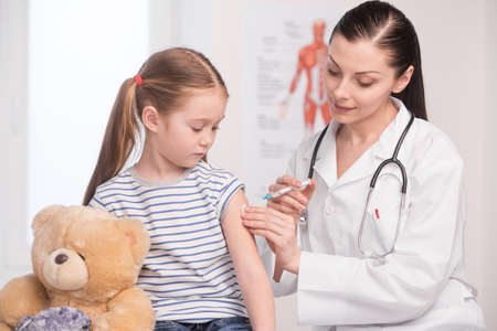 Injection. Confident young doctor in lab coat doing injection to a little girl photo
