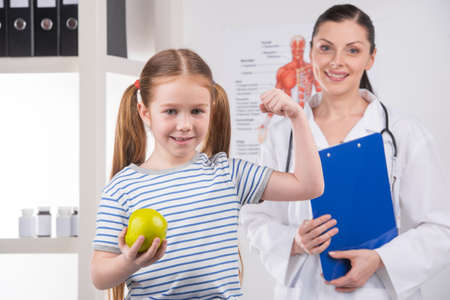 Healthy little girl. Cheerful little girl holding apple and smiling while doctor standing on background photo