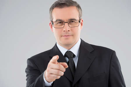 50s adult: Confident businessman. Portrait of confident middle-age man in formalwear pointing you while isolated on grey