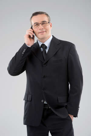 Confident businessman. Confident middle-age man in formalwear talking on the mobile phone isolated on grey photo