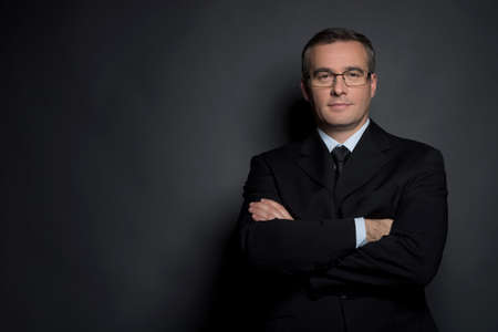 Confident businessman. Confident middle-age man in formalwear keeping his arms crossed and looking at camera while standing isolated on grey photo