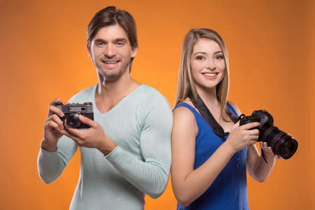 Photographers. Two cheerful photographers holding cameras in their hands and smiling while isolated on coloured background photo