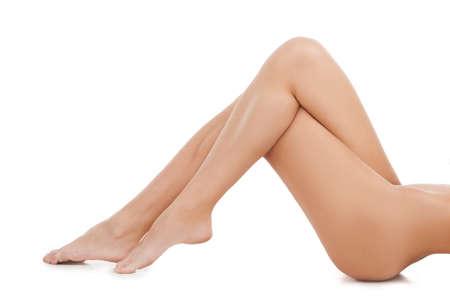 corps femme nue: Femme nue. Image recadrée de jeunes femmes nues couché sur le dos et de garder les jambes croisées au genou alors isolé sur blanc Banque d'images
