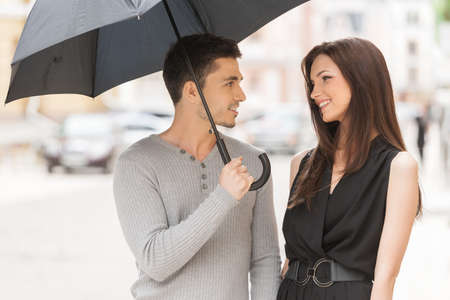 Loving couple. Cheerful young couple standing close to each other while man holding umbrella photo
