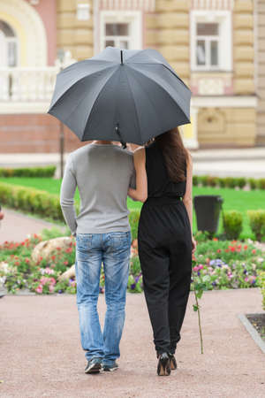 Loving couple with umbrella. Rear view of young couple walking on street while man holding umbrella photo