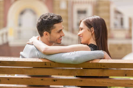 sitting on a bench: Loving couple on the bench. Rear view of cheerful young couple sitting close to each other on the bench and smiling Stock Photo