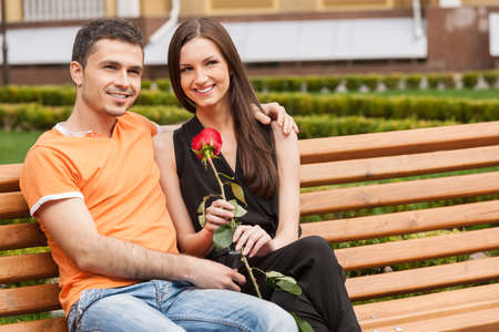 Loving couple on the bench. Beautiful young loving couple sitting close to each other on the bench and smiling photo