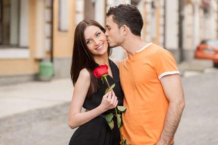pareja besandose: Beso. Alegre joven pareja abraz�ndose mientras que el hombre besa a su novia en la mejilla