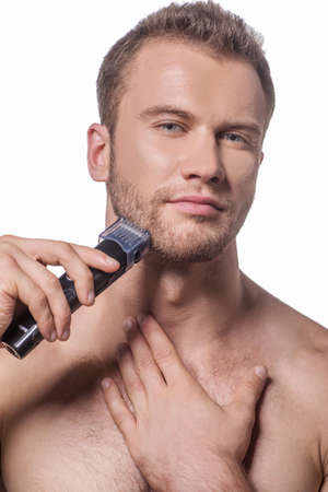 electric razor: Man shaving. Handsome young shirtless man shaving with electric razor