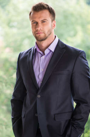 Confident businessman. Handsome young man in formalwear looking away Stock Photo