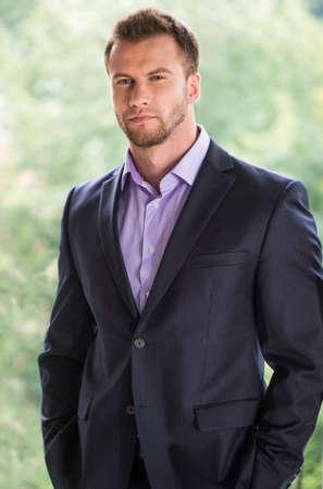 Hombre de negocios confidente. Apuesto joven en ropa formal mirando a otro lado