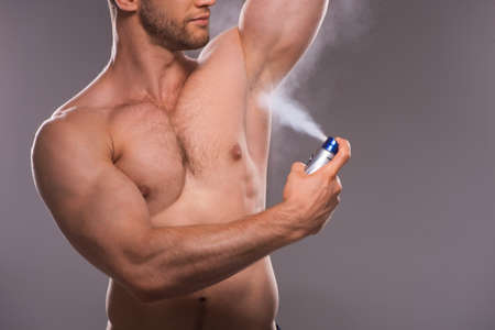Man shaving. Handsome young shirtless man shaving with electric razor