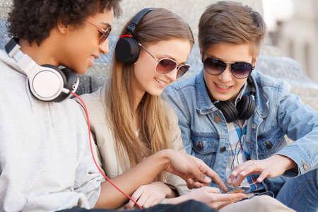 escuchando musica: Amigos adolescentes. Tres alegres amigos adolescentes sentados cerca uno del otro y escuchar la m�sica