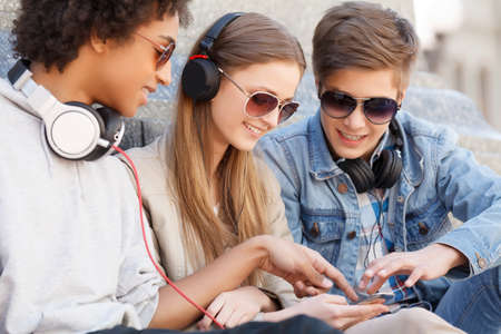 only teenagers: Teenage friends. Three cheerful teenage friends sitting close to each other and listening to the music