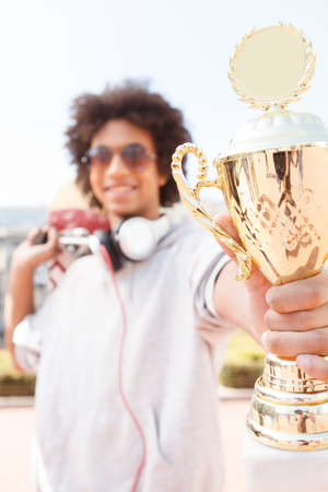 low prizes: Teenager. Cheerful African descent teenager showing trophy and smiling Stock Photo