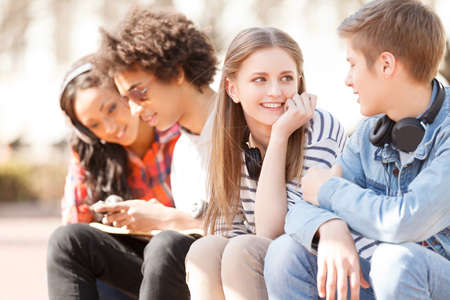 youth culture: Teenage friends. Four cheerful teenage friends talking to each other