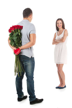 Loving couple. Full length of handsome man holding bunch of flowers and looking at his girlfriend isolated on white photo