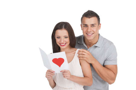 Loving couple. Beautiful young loving couple standing isolated on white while woman holding greeting card photo