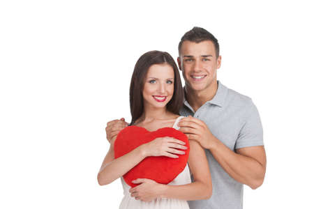 Loving couple. Beautiful young loving couple standing isolated on white while woman holding heart shape pillow photo