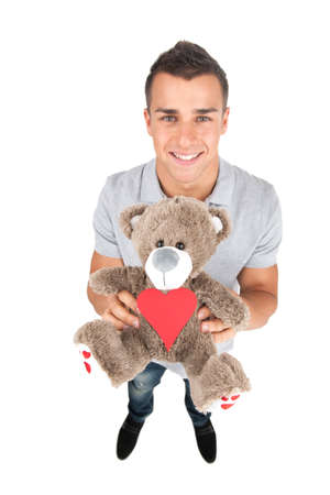 valentine s day teddy bear: Man with toy bear  Top view of handsome young man holding a toy bear while standing against white background