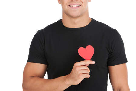 man s: Man with paper heart  Cropped image of handsome young man holding a paper heart while standing against white background