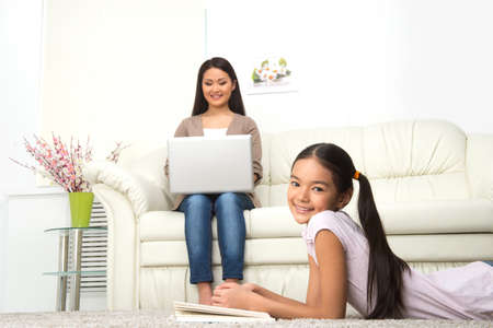 Mother and daughter at home. Cheerful woman working on laptop while her daughter reading book near her photo