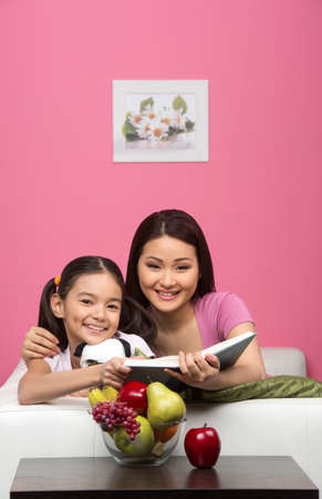 Mother and daughter at home. Mother and daughter reading book together and smiling photo