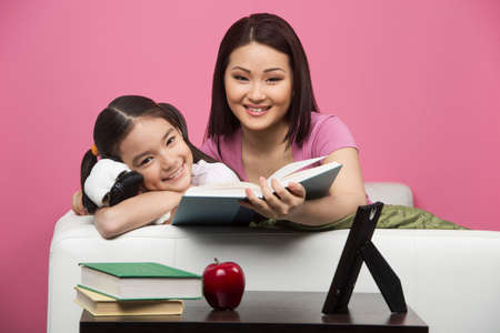 Mother and daughter at home. Cheerful mother and daughter reading book together and smiling photo