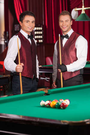 cues: Pool players. Two cheerful young pool players holding cues and looking at camera