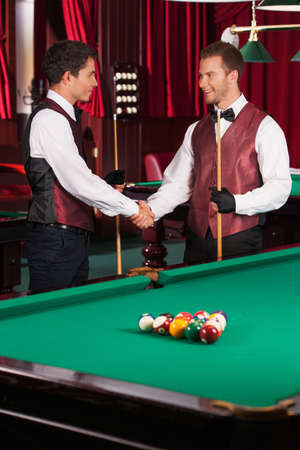 pool table: Pool players. Two cheerful young pool players handshaking and smiling Stock Photo