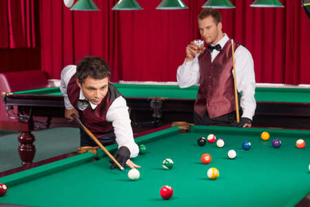 Playing pool. Two confident young men playing pool while one of them drinking whiskey photo