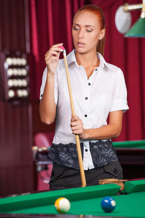 pool cue: Pool player. Confident young woman holding pool cue Stock Photo
