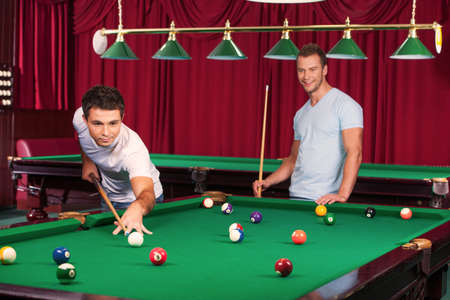 pool table: Pool game. Confident young man aiming the billiard ball with cue while his opponent  holding billiard cue and smiling on the background Stock Photo